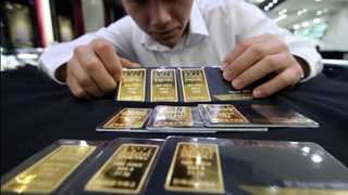 Gold drops as dollar holds higher amid debt auctions